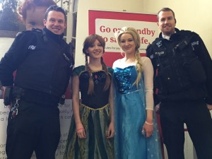 Policemen arrive to register and are accosted by the cast of Frozen