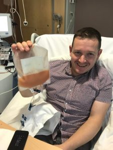 Rob holding up his stem cells, during donation